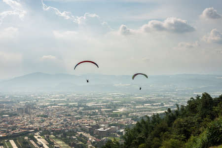 colorful paragliding over blue sky with white clouds in the town, Puli, Taiwan