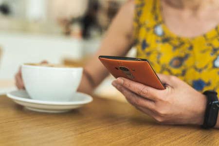 Mujer con teléfono celular en una cafetería durante el día Foto de archivo
