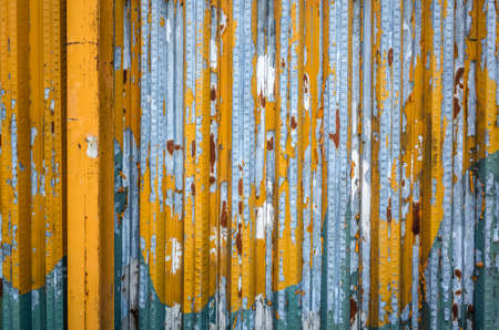 weathered metal wall in yellow and blue color