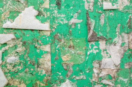 grungy green billboard wall with old tape residue