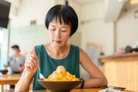 mature Asian woman eat mango shave ice Stock Photo