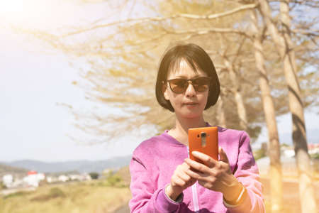 mature Asian woman using the smart phone at outdoor Stok Fotoğraf