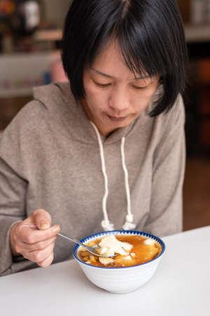 Asian woman eat tofu pudding at a store 写真素材 - 129696306