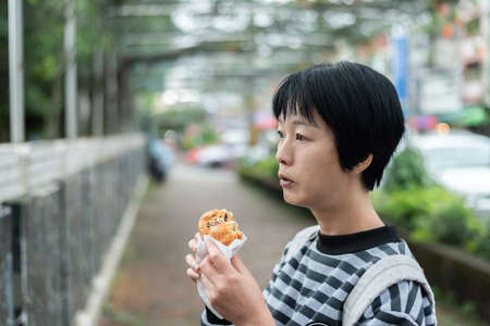 woman eat traditional Taiwanese snack at a street Reklamní fotografie - 129697263