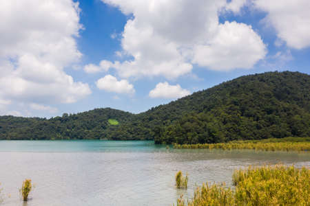 landscape of beautiful mountains and grassland with water in Sun Moon Lake at Nantou, Taiwan 스톡 콘텐츠
