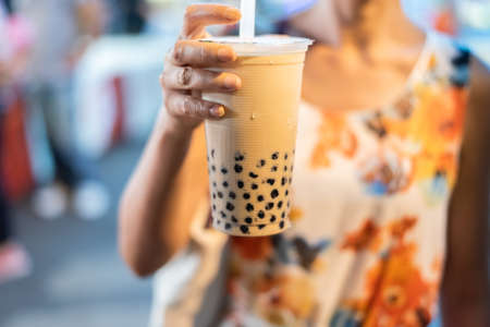 Asian woman holding the famous taiwanese bubble milk tea at night market Reklamní fotografie