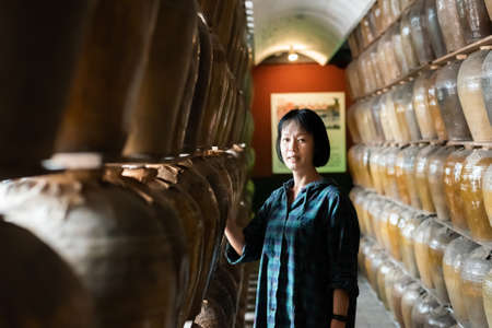 mature Asian woman stand with old pottery at Puli Brewery, Taiwan