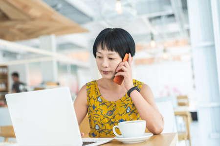 Mujer escucha en el teléfono móvil y trabaja en la cafetería.