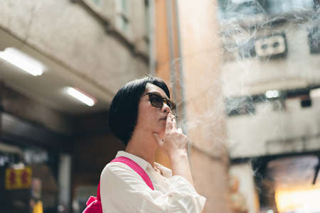 Asian woman traveling and smoking in the traditional marketplace at Taiwan Imagens
