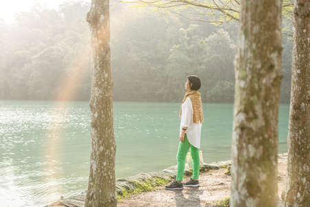 traveling Asian woman stand near the lake under trees at Sun Moon Lake, Nantou, Taiwan