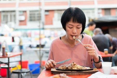 mature woman eat Taiwanese night market steak at the street