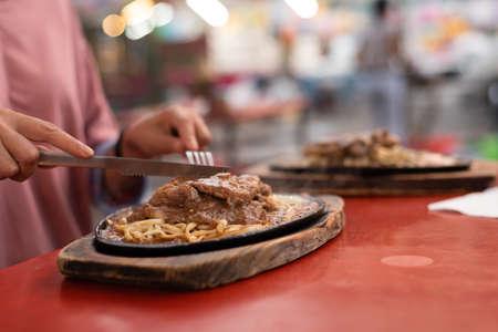 woman eat Taiwanese night market steak at the street Reklamní fotografie
