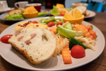 breakfast of bread, vegetables and fruits on a dish in the morning