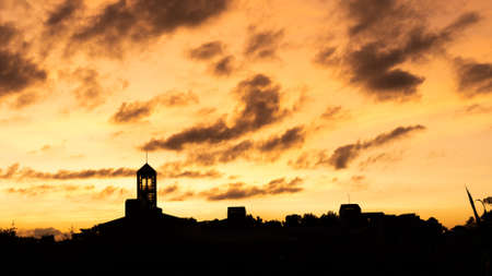 sunset landscape with dramatic clouds over the silhouette tower in a city