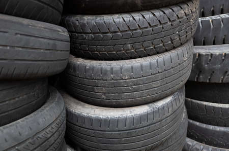 old used car tires stacked in piles in the daytime