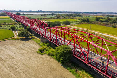 red famous Xilou Bridge over the river and farm in Yunlin county, Taiwan
