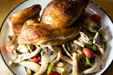roasted chicken leg with mushrooms on a plate Stockfoto