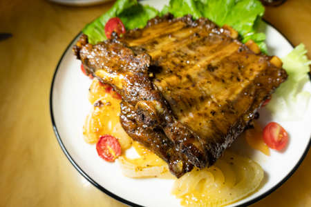 grilled pork ribs with vegetable on a plate at home