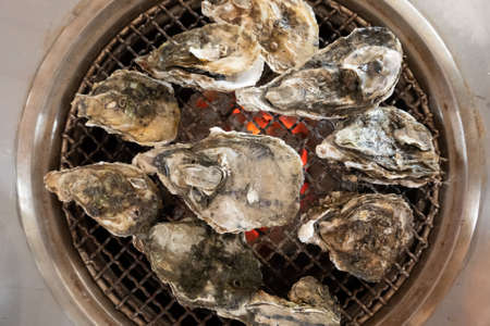 fresh oysters on barbecue grill in a restaurant at Taiwan