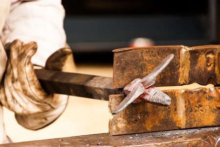forger: Blacksmith working a metal piece with the hammer on a craftsmens market. Stock Photo