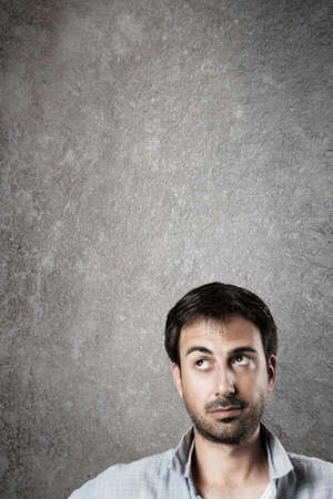 looking up: Man expectantly looking up with raised eyebrow. Vertical image.