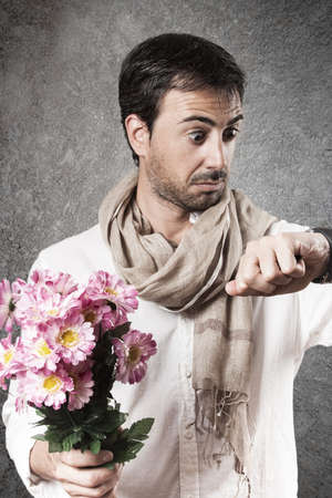 looking at watch: Man in love with a bouquet of flowers looking watch with concern. Vertical image.