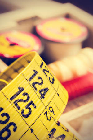tailor measuring tape: Yellow tailor measuring tape close up with spools of thread in a retro vintage style. Vertical image. Stock Photo
