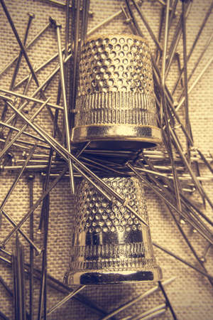 old tools: Pins and thimbles on a piece of cloth seen from above. Vintage style. Vertical  image. Stock Photo
