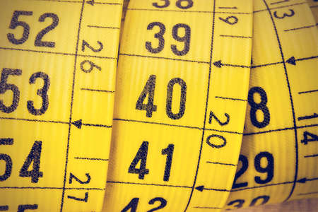 tailor measuring tape: Yellow tailor measuring tape macro in a retro vintage style. Horizontal image. Stock Photo