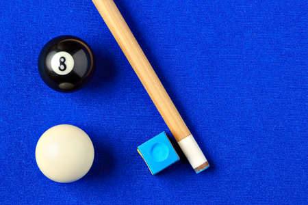 pool cue: Billiard balls, cue and chalk on a blue pool table. Viewed from above. Horizontal image.
