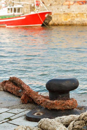 Iron pier in the harbour with a big rope. Vertical image.