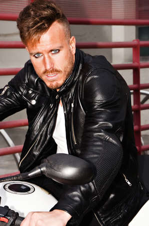 defiant: Trendy young man with black leather jacket on a motorcycle with a defiant look. Vertical image.