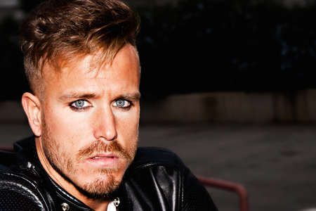 horizontal haircut: Portrait of a fashionable young man with blue eyes, stylish haircut and posing with a black jacket. Close up. Copy-space. Horizontal image. Stock Photo
