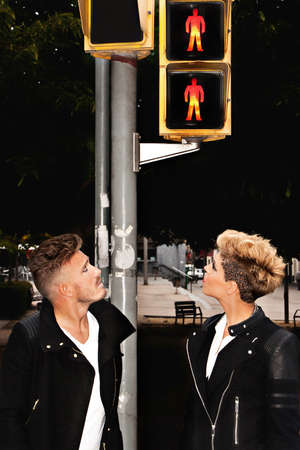 attractive male: Trendy young couple looking at the traffic light in the middle of the street. Urban fashion photography. Vertical image.