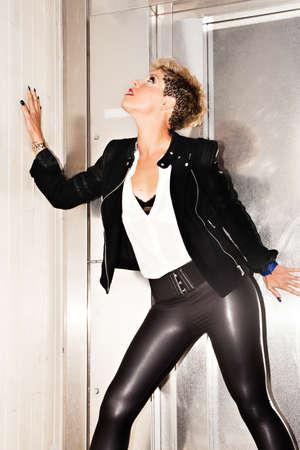 urban fashion: Fashionable woman in seductive position. Urban fashion photography. Vertical image.