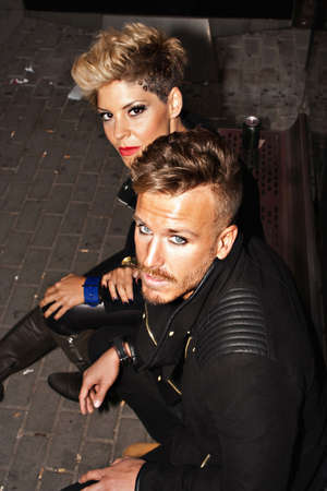 modelos hombres: la pareja de moda que se sienta en la parada de autob�s con mirada desafiante. la fotograf�a de moda urbana. vertical de la imagen.