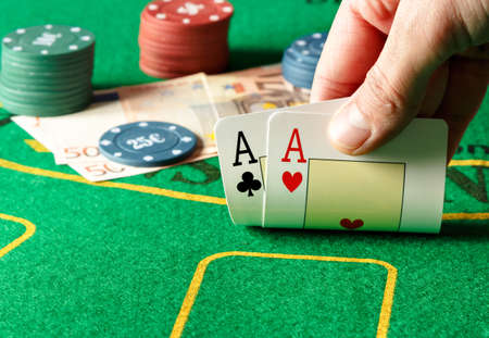 poker player: Closeup of poker player with two aces on a poker table. Horizontal image. Stock Photo