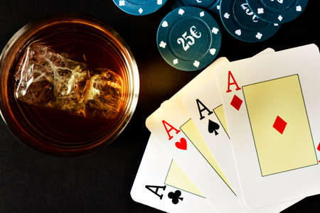 aces: Poker of aces with poker chips and whiskey viewed from above. Horizontal image.