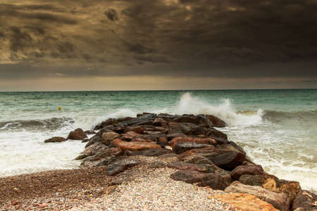 breakwaters: Storm over breakwaters of the beach. Horizontal image. Stock Photo