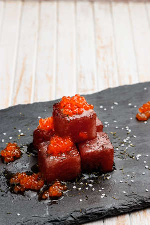 Tuna sashimi dipped in soy sauce with salmon roe, thick salt and dill on slate stone. Raw fish in traditional Japanese style. Vertical image. Stock Photo