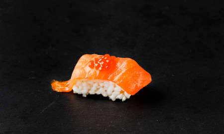 Salmon Nigiri with salmon roe on black slate stone.Raw fish in traditional Japanese sushi style. Horizontal image. Stock Photo