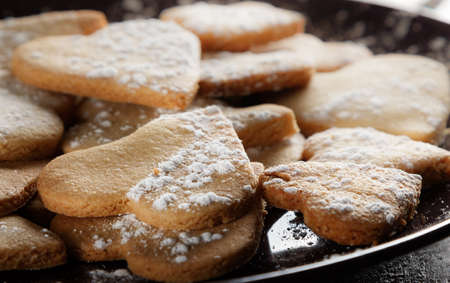 Delicious home-made heart-shaped cookies sprinkled with icing sugar on sackcloth and wooden boards. Horizontal image seen against backlight.