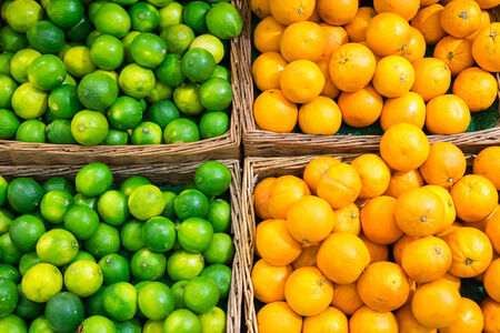 Limes and oranges for sale at a market photo