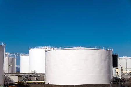 storage tanks: White storage tanks in front of a blue sky