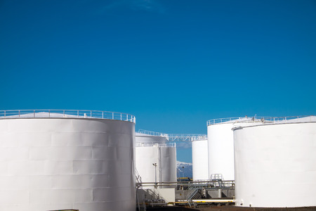 storage tanks: White gas storage tanks in front of a blue sky