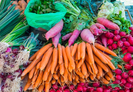 herbage: Carrots, radish and herbage for sale at a market Stock Photo