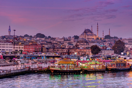 eminonu: ISTANBUL, TURKEY - OCTOBER 20, 2015: Fisher boats and mosque in Eminonu District at dawn Editorial