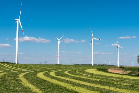 nonpolluting: Wind Wheels in a mowed field of hay, seen in Germany