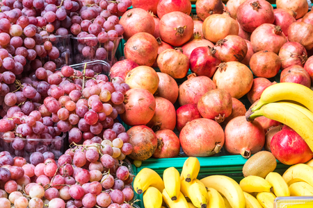 edibles: Grapes, bananas and pomegranate for sale at a market