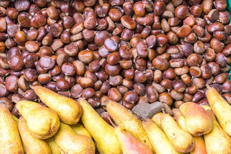 Brown chestnuts and yellow pears for sale at a market